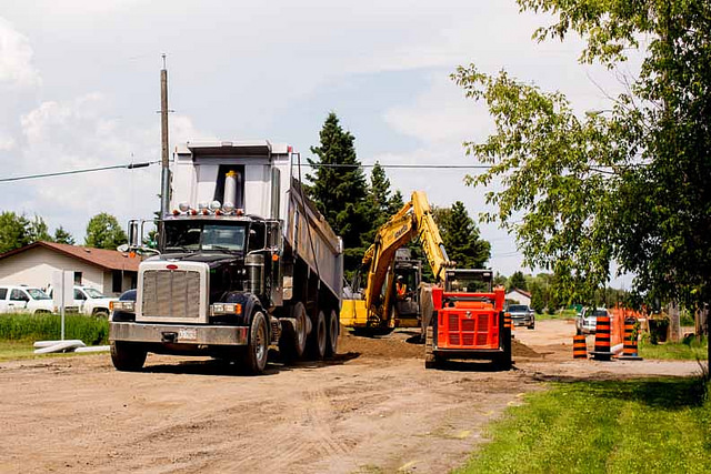 A dump truck, loader and small cat are all on a road at the Fort William First Nation housing project.