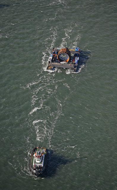 Tugboats pull a barge containing the OpenHydro turbine into position near Parrsboro, Nova Scotia, in November 2009.