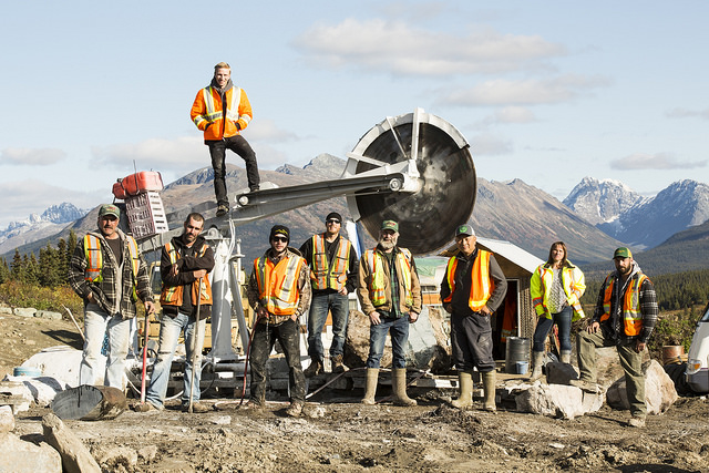 The Bunces and the crew pose next to one of their saws in the field.
