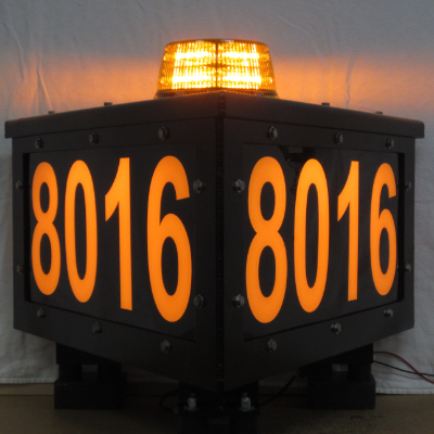 A lit-up, three-sided sign with a light on top and the numbers 8016 on the side.