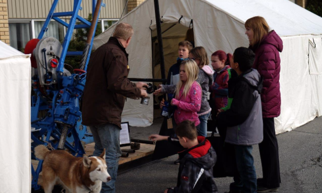 Farren Billey of FB Drilling shows elementary school students how a diamond drill rig works. The drill rig is the chamber's educational-relations centrepiece.