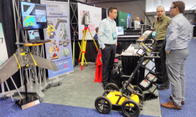 Peter Willis and Parker Adams speak with a delegate at the Spatial Technologies booth.