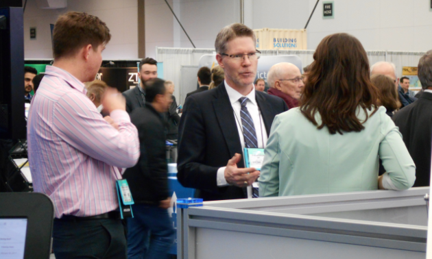Gavin Dirom, the President and CEO of the AME, speaks with delegates at the TECK booth.