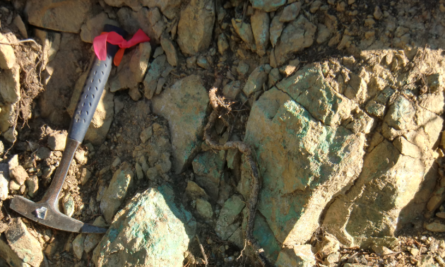 A tool rests next to a rock of minerals