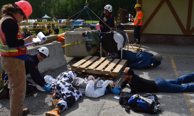 Mine rescue workers try to free a man trapped under a woman dressed in a cow costume