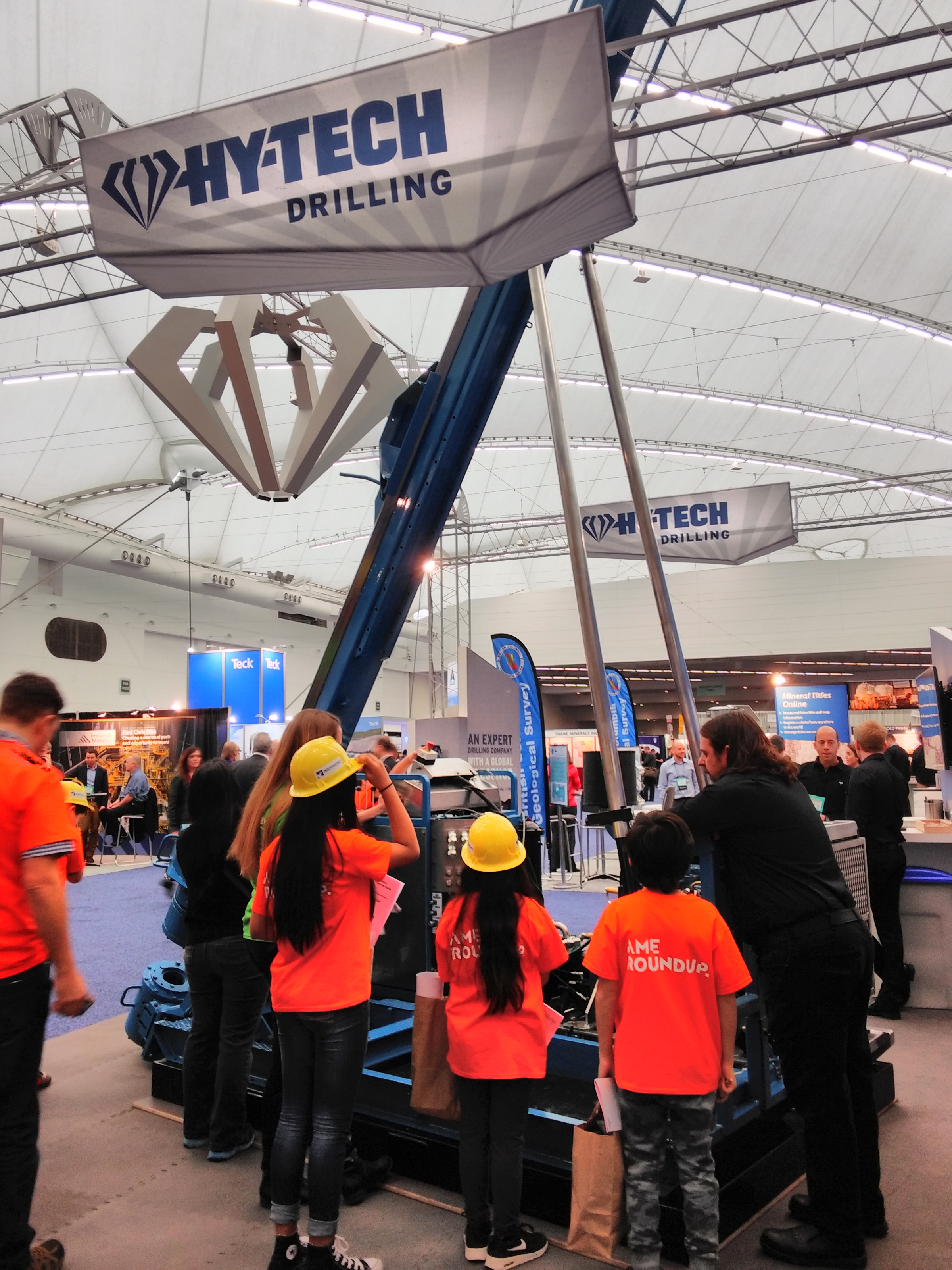 Hy-Tech Drilling Ltd. displayed a tall eye-catching drill. Students and their guide are given an explanation of how a drill is used in the field.