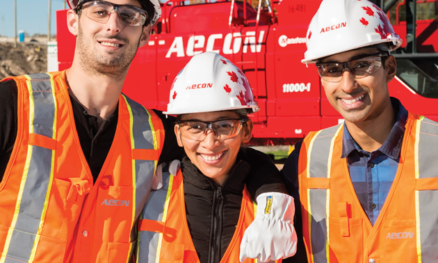 Workers with hard hats, standing in front of AECON heavy equipment.