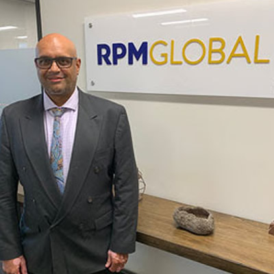 Akoo Patel, standing in front of RPMGlobal sign.