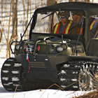 an all-terrain vehicle on tracks carrying workers over snow