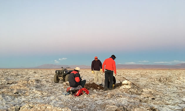 A group of people working in a dry, desert area.