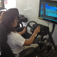 A woman sits behind a simulator steering wheel with a scenario being represented on screen.