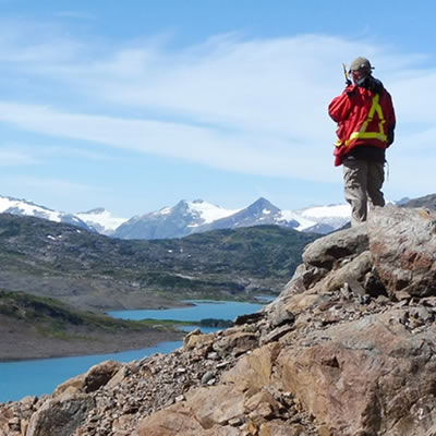 Man standing on top of mountainside, looking down at water.