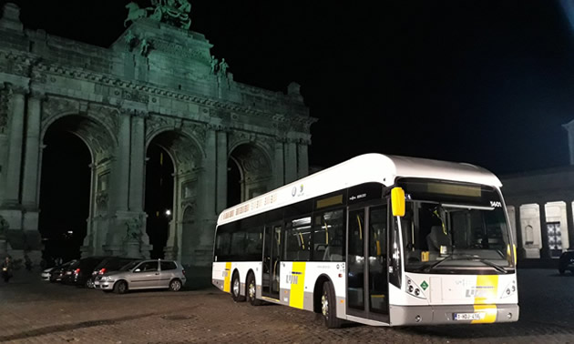 Passenger bus parked in front of monument at night.