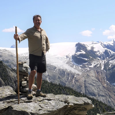 Bruce Madu is standing on a rocky mountaintop with a walking stick near Roger's Pass along the Trans-Canada Highway west of Field, B.C.