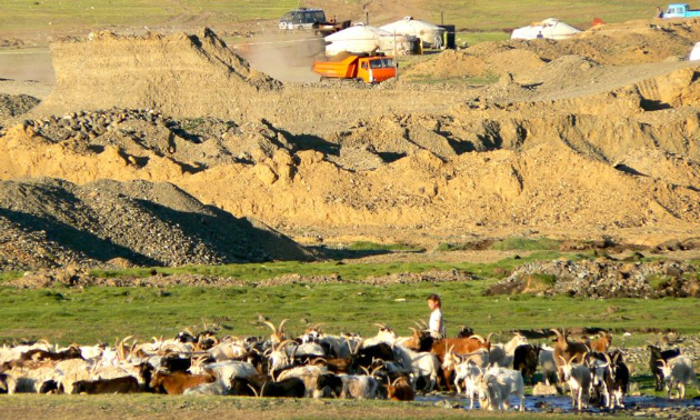 A Mongolian herder with a mining operation in the background