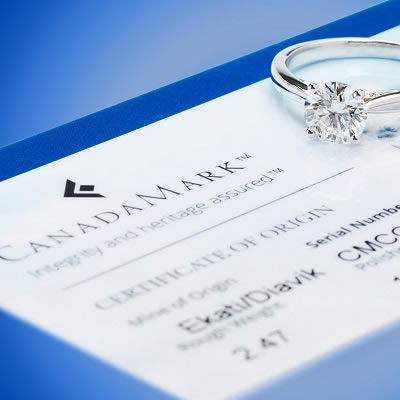 Canadamark certificate with diamond ring sitting on top of paperwork.