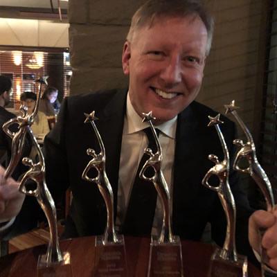 Chris Gardner, ICBA president, shows off six prestigious Reed Awards.