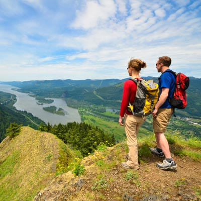Two people standing on mountain top looking down at river.
