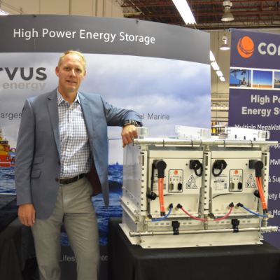 Andrew Morden, CEO of Corvus Energy stands beside a bank of their heavy-duty industrial batteries capable of powering large ferries and other marine vessels.