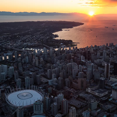 Scenic view of downtown Vancouver, with sun setting in distance.