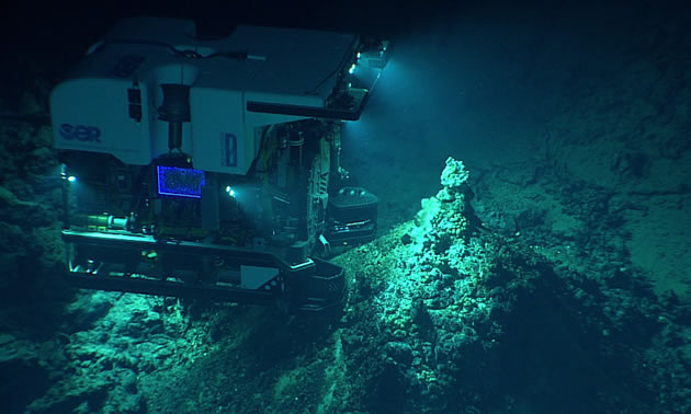 A remotely-operated underwater vehicle images a hydrothermal vent in the deep ocean.