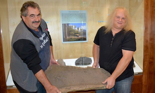 Guy Santucci, Cranbrook History Centre Board Chair, and Jason Jacob, President of East Kootenay Chamber of Mines, with one of the dino prints.
