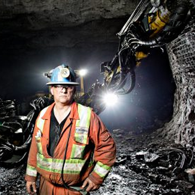 Miner standing underground in front of mining equipment.