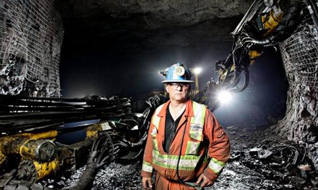 Miner standing underground in front of mining equipment.