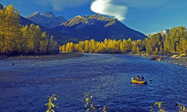 A yellow boat with fishermen floats down a deep blue river against a stunning backdrop of trees and mountains