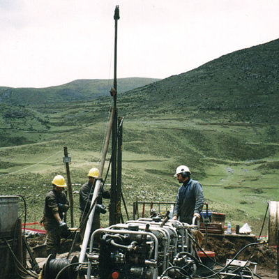 Group of workers using mining equipment in the field.