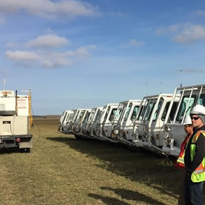 Picture of trucks lined up in field, with technicians monitoring equipment.