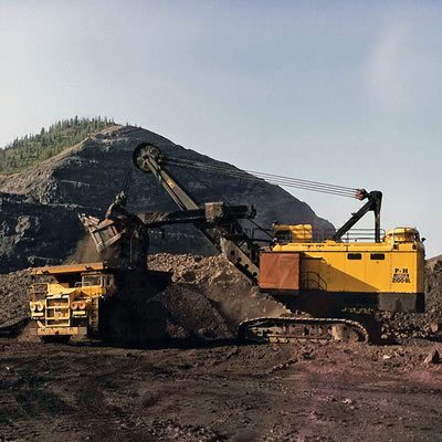 A yellow Teck truck shovel in front of a large pile of coal