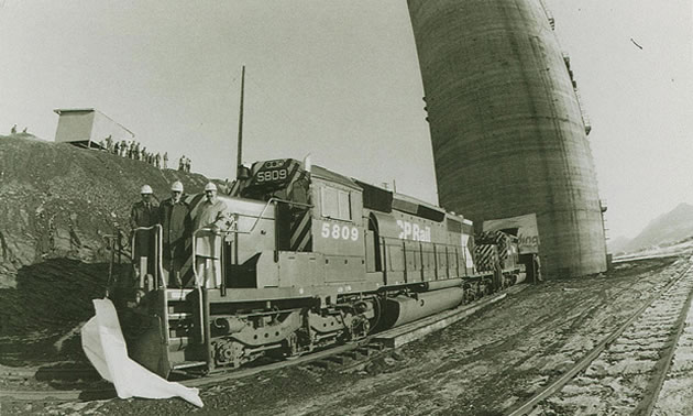 A black and white photo of three man on a CPR engine in front of a tall silo