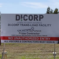 Di-Corp employees standing by company sign