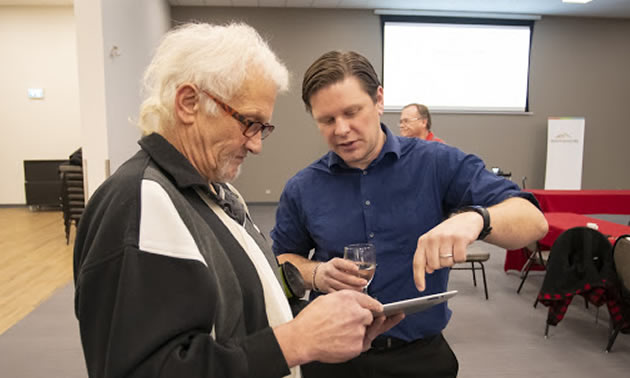Geoscience representative discussing info at open house with a man.