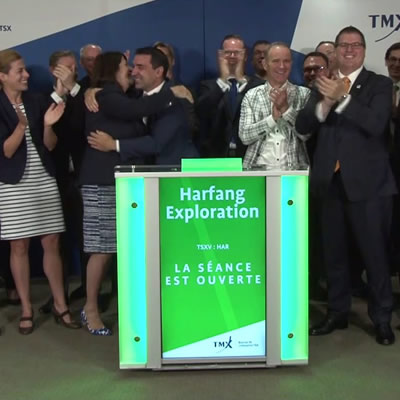Group of people standing at podium, smiling, clapping and congratulating each other.