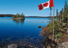 A smooth, clear blue lake with a small treed island and treed shoreline; a Canadian flag flies on the right side