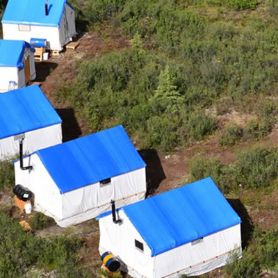 Overhead view of portable mining accommodations with blue roofs.