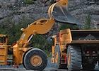 A large loader dumps its shovel into a dump truck