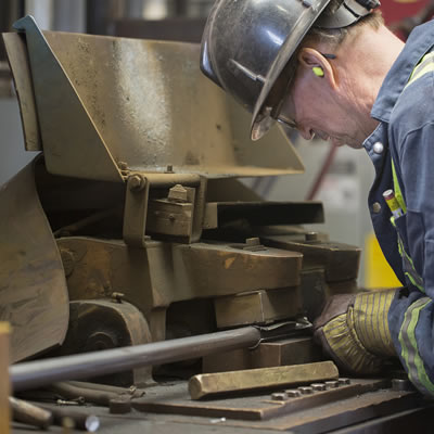 Lifting Services employee grinding a steel rod on a machine.