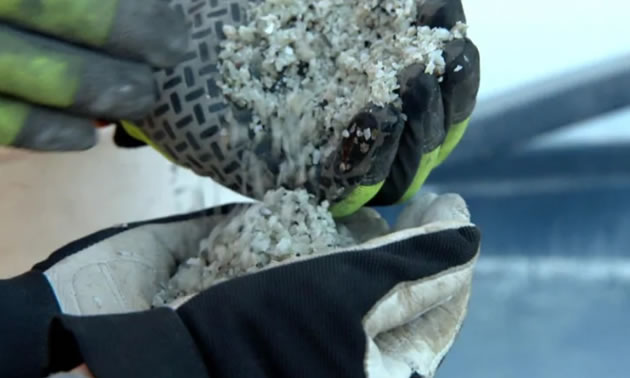 Close up of lithium being poured from one gloved hand to another.