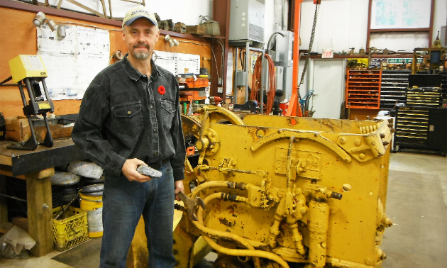 Brian Mills poses with Galena silver-lead-zinc and an Eimco mucking machine, used to scoop ore into ore cars.