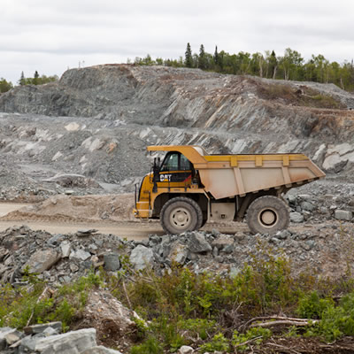 Picture of open pit mine surrounded by forest, with large CAT mining vehicle in foreground of photo.