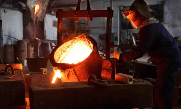 Worker pouring molten gold.