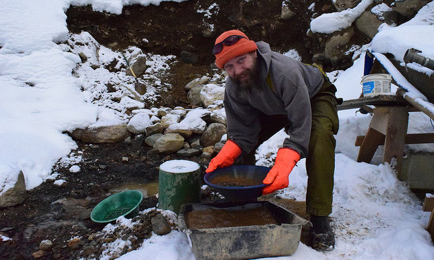 Lathem whirls the pan in water to remove the larger stones, leaving only a sandy sludge.