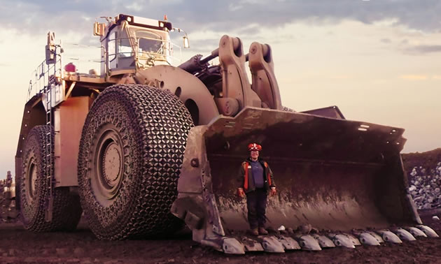 Large piece of machinery with person standing in bucket.