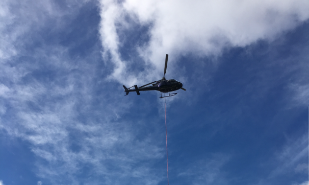 A helicopter is slinging casings for Avataa Rouillier Drilling's current drilling operation south of Kuujjuaq in Nunavik.