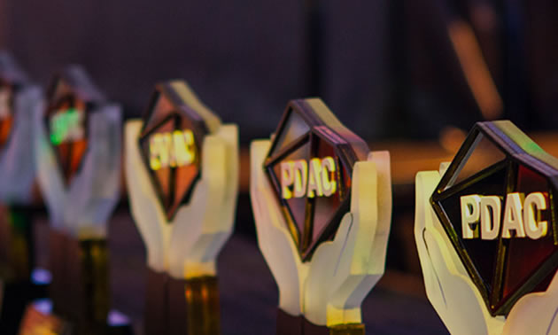 Close-up picture of PDAC Award, showing two stylized white hands holding up a transparent diamond shape printed with PDAC logo.