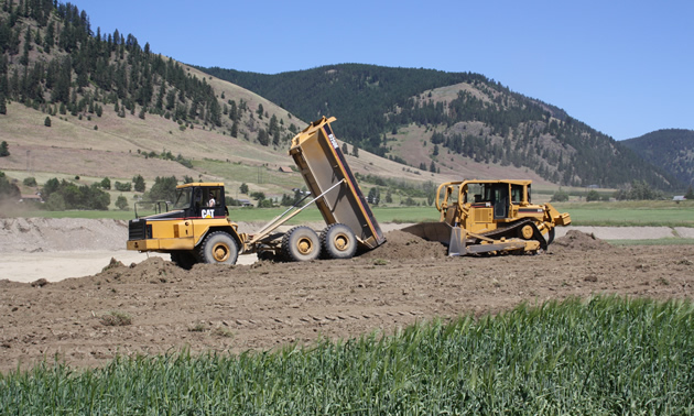 a dumptruck and dozer working