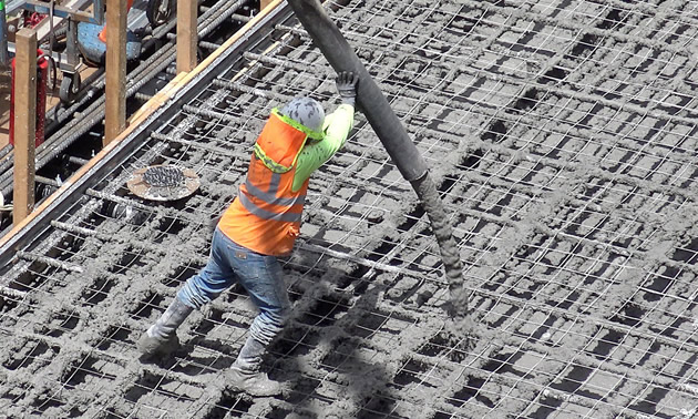 Worker pouring concrete onto steel girders.